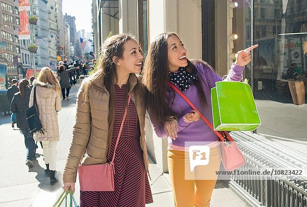 Young female adult twins carrying shopping bags pointing at city shop window