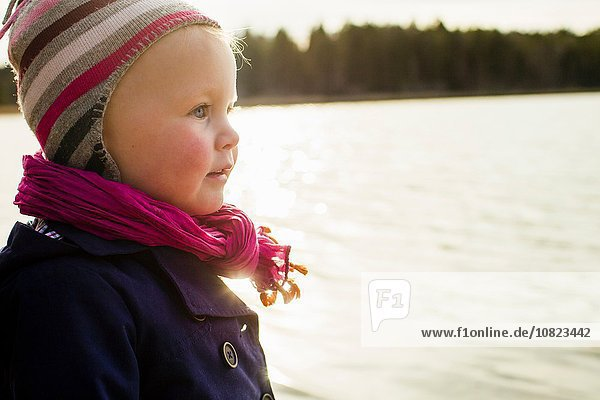 Portrait of cute female toddler looking out over lake