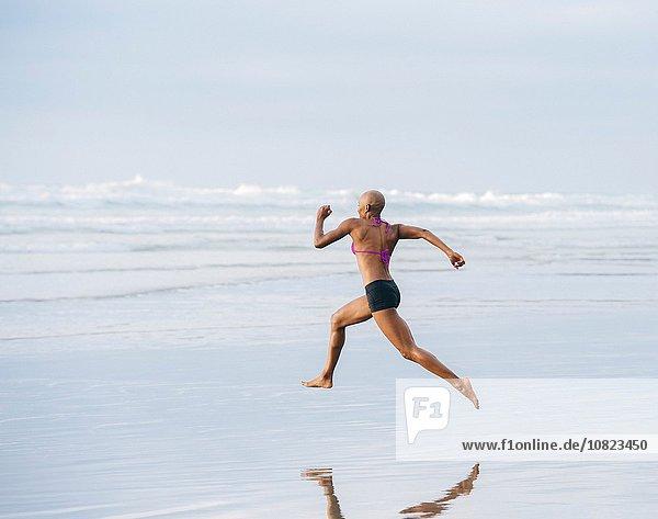 Woman in bikini sprinting on beach
