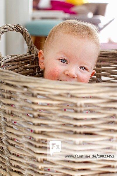Portrait of cute female toddler hiding in wicker basket