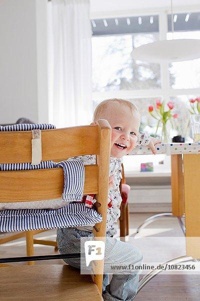 Portrait of female toddler sitting looking over her shoulder