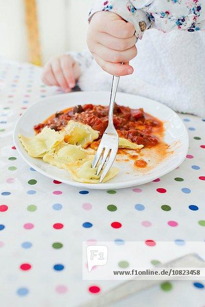 Cropped shot of female toddler eating ravioli at table