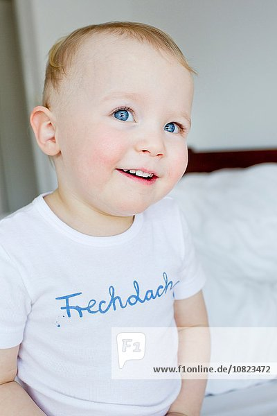 Portrait of cute blue eyed female toddler sitting on bed