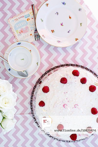 Overhead view of birthday tea party table with birthday cake and card