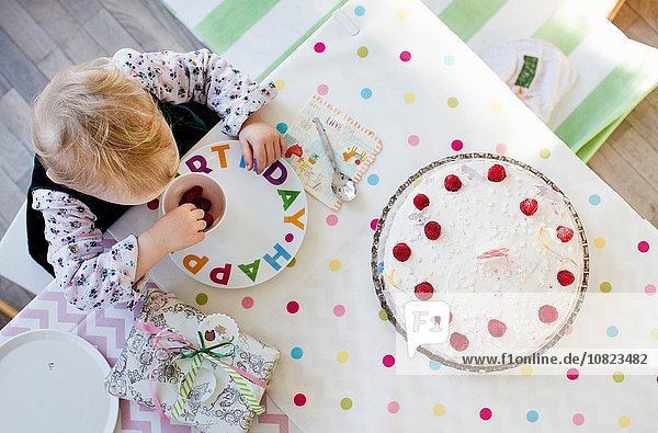 Overhead view of female toddler eating raspberries at birthday tea party table
