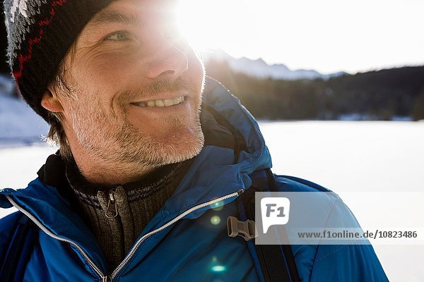 Close up sunlit portrait of mature man hiking in snow covered landscape,  Berg,  Bavaria,  Germany