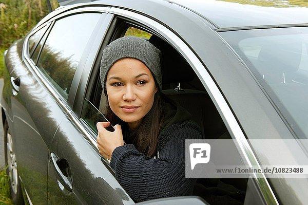 Junge Frau  die sich lehnt und aus dem geparkten Autofenster blickt