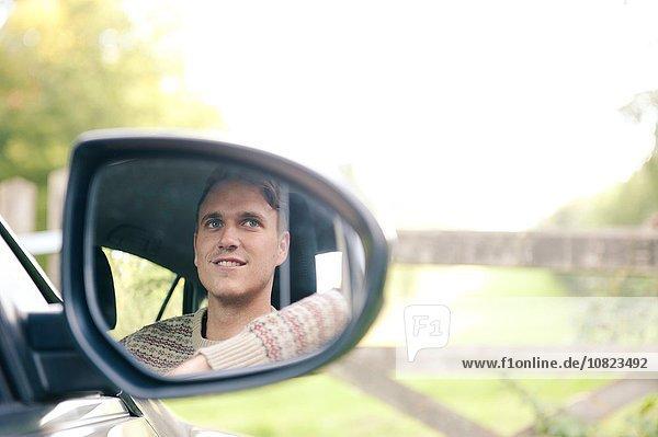 Flügelspiegel Spiegelung eines jungen Mannes im Auto  der am ländlichen Tor parkt.