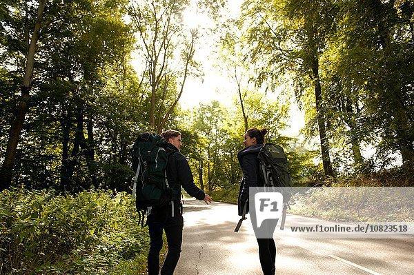 Rückansicht des jungen Wanderpaares beim Plaudern auf der Landstraße