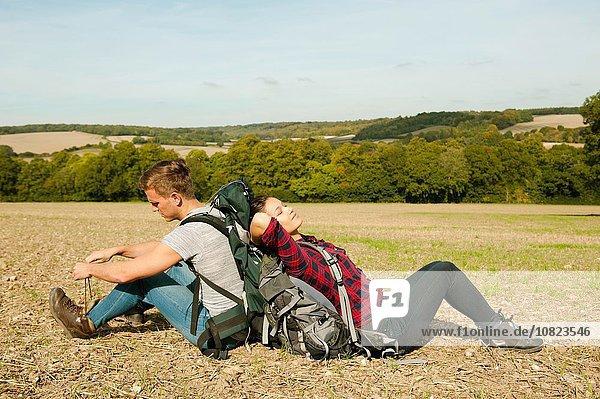 Junges Wanderpaar Rücken an Rücken im Feld  Great Missenden  Buckinghamshire  Großbritannien