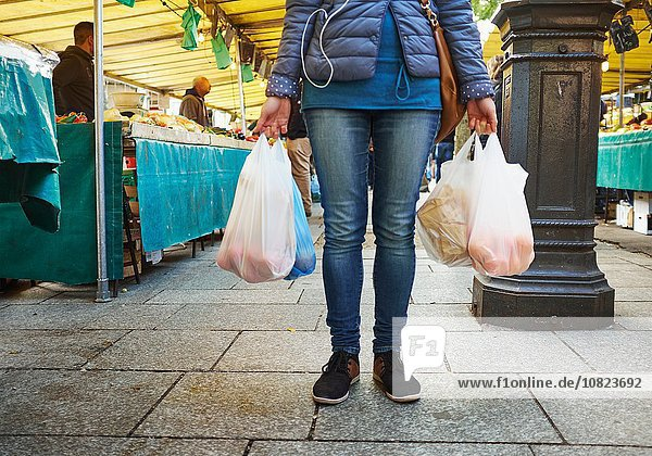 Young woman at market  holding bags of shopping  low section