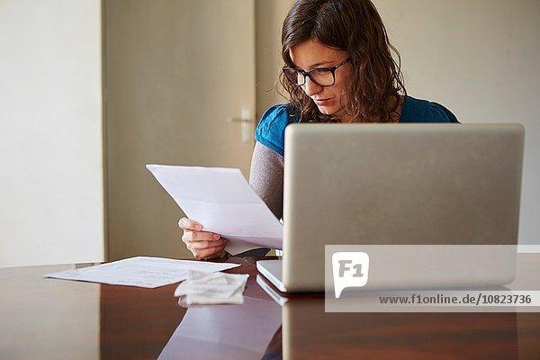 Junge Frau sitzt am Tisch mit dem Laptop und schaut sich den Papierkram an.