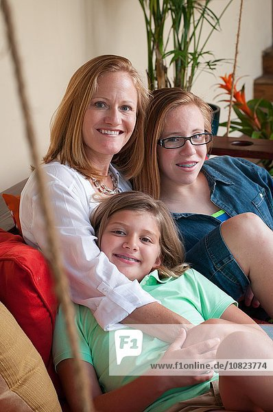 Mother sitting with daughters looking at camera smiling