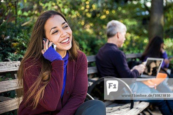 Junge Frau sitzt auf der Parkbank und plaudert auf dem Smartphone.