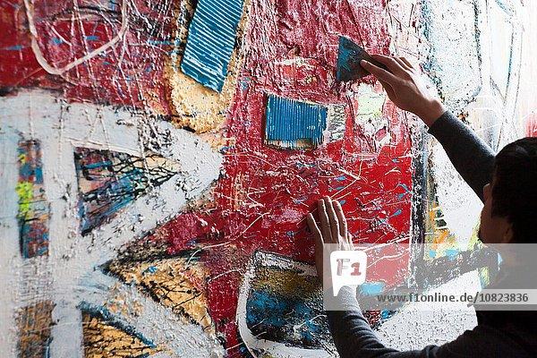 Männlicher Künstler schafft gemaltes Kunstwerk