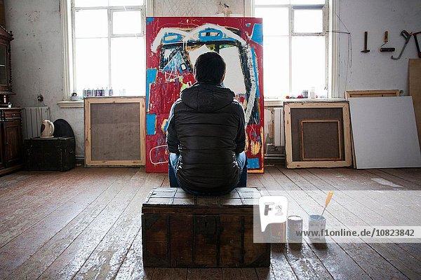 Künstler auf Kiste sitzend  Kunstwerk betrachtend  Rückansicht
