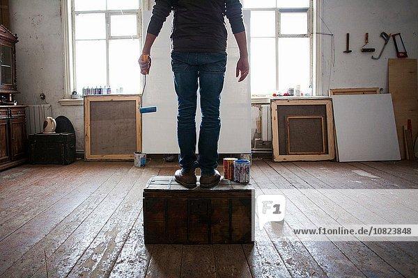 Männlicher Künstler auf Kiste sitzend  auf leere Leinwand schauend  niedriger Schnitt