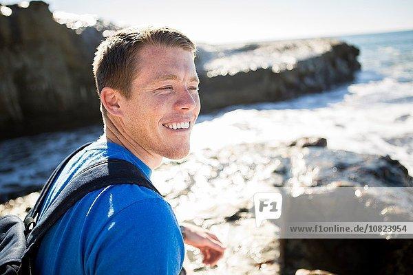 Junger Mann am Meer  lächelnd