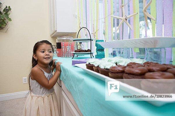 Junges Mädchen schaut sehnsüchtig auf Kuchen auf Küchenarbeitsplatte
