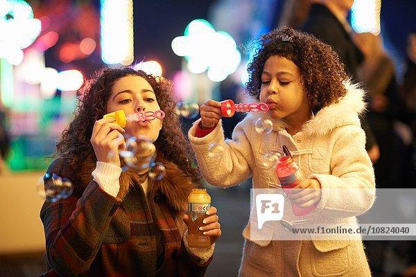 Mutter und Tochter blasen Blasen  auf der Kirmes