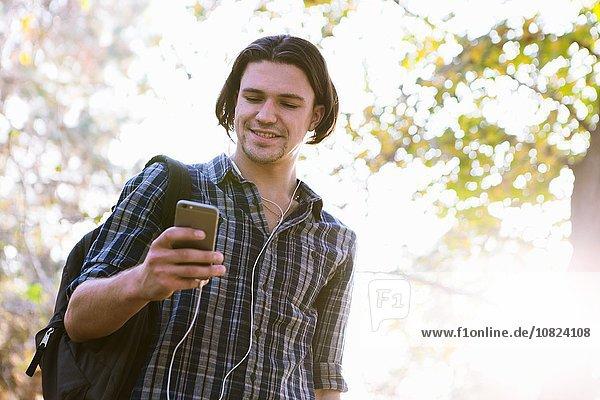 Niedriger Blickwinkel des jungen Mannes  der das Smartphone hält und lächelnd nach unten schaut.