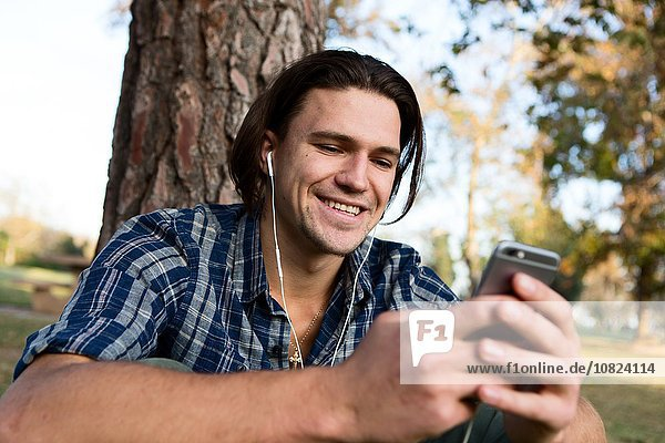 Junger Mann am Baum sitzend mit Kopfhörern und lächelndem Blick auf das Smartphone