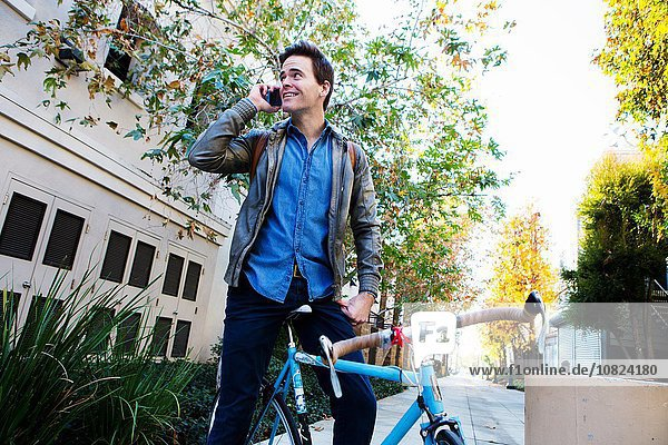 Junger Mann auf dem Fahrrad im Chat auf dem Smartphone