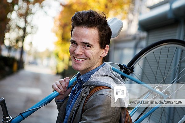 Portrait of young man carrying cycle on shoulders along sidewalk