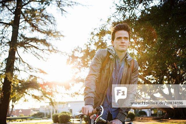 Junger Mann mit Fahrrad wartend und wegschauend