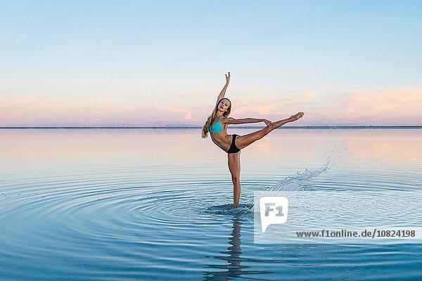 Female ballet dancer poised on one leg in lake  Bonneville Salt Flats  Utah  USA