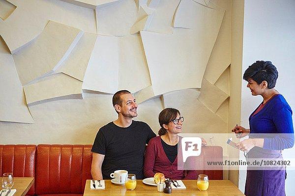 Kellnerin nimmt die Bestellung im Restaurant vom mittleren erwachsenen Paar entgegen.