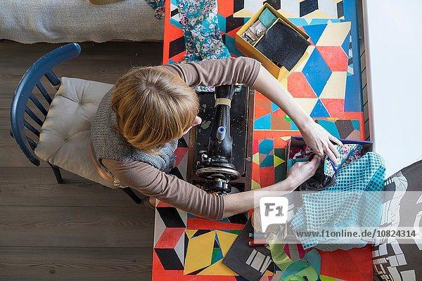 Overhead-Ansicht der Frau mit Vintage-Nähmaschine bei der Stoffauswahl