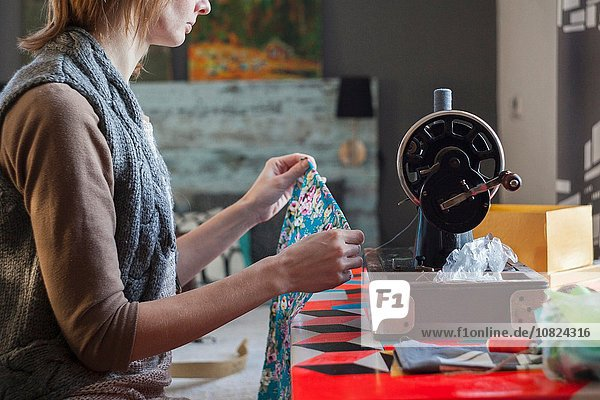 Frau mit Vintage-Nähmaschine bei der Stoffkontrolle am Tisch
