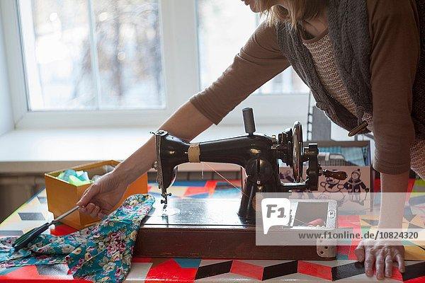 Frau mit Vintage-Nähmaschine greift nach der Schere am Tisch