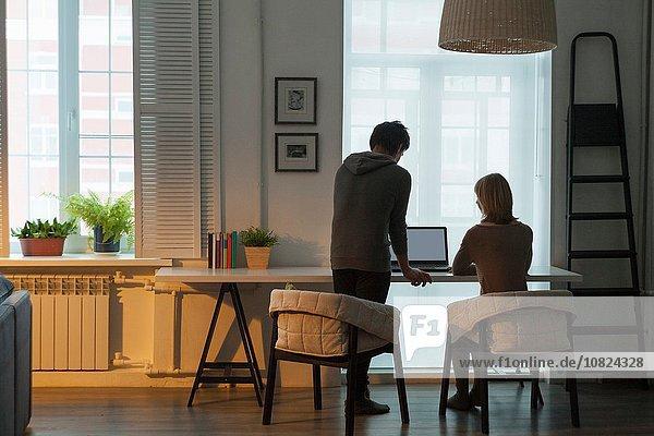 Rückansicht des mittleren erwachsenen Paares mit Laptop am Tisch vor dem Fenster