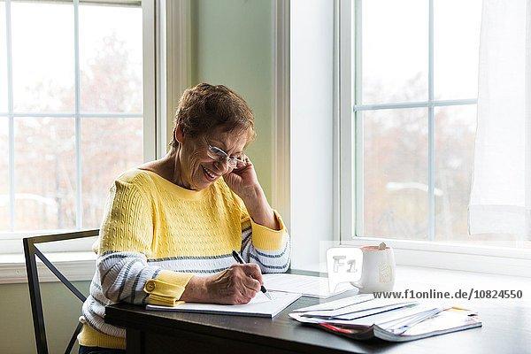 Senior Senioren Frau Schreibtisch Fröhlichkeit schreiben
