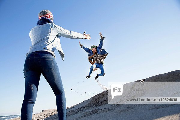 Junge Frau beobachtet einen Freund  der über eine Sanddüne springt.