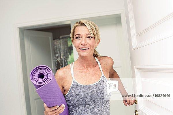 Reife Frau an der Haustür mit Yogamatte