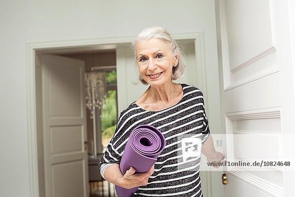 Seniorin an der Haustür mit Yogamatte