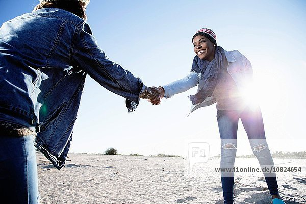 Two friends fooling around at beach  holding hands  smiling