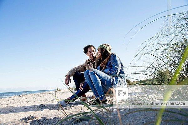 Junges Paar entspannt am Strand  von Angesicht zu Angesicht  lächelnd