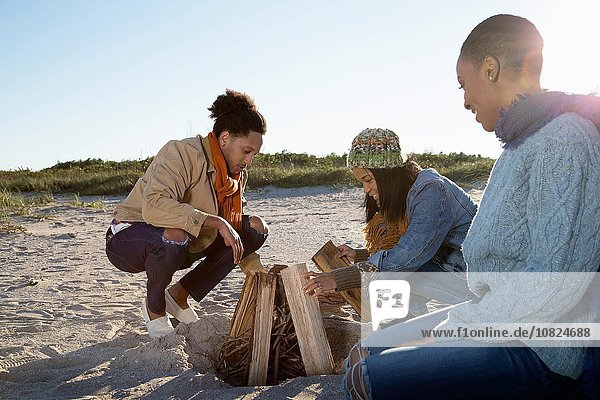Three friends on beach  preparing camp fire