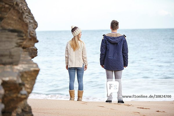 Rear view of young couple looking out from beach  Constantine Bay  Cornwall  UK