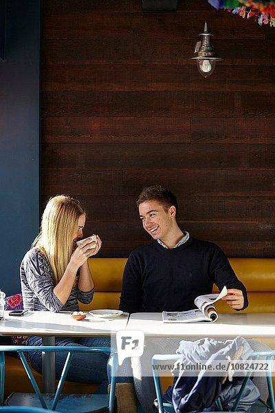 Junges Paar auf Date im Cafe beim Kaffeetrinken und Lesemagazin
