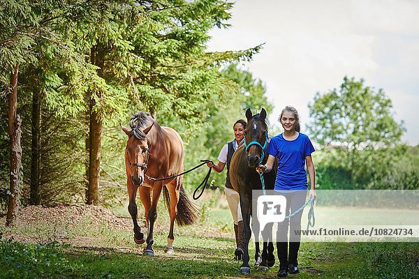 Durchgehende Vorderansicht des Mädchens und der reifen Frau  die das Bleiseil hält und mit Pferden geht  die lächelnd in die Kamera schauen.