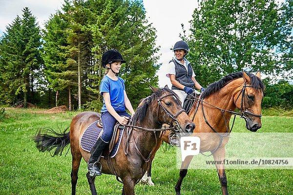 Reife Frau und Mädchen zu Pferd mit lächelndem Reiterhut