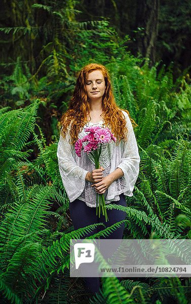 Young woman holding bunch of pink gerberas amongst forest ferns