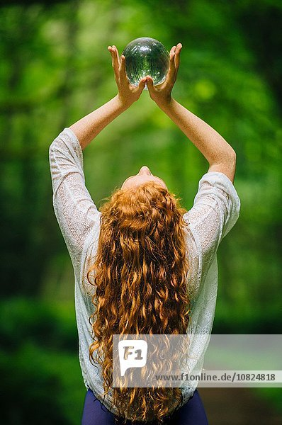Rear view of young woman with long red hair holding up crystal ball in forest