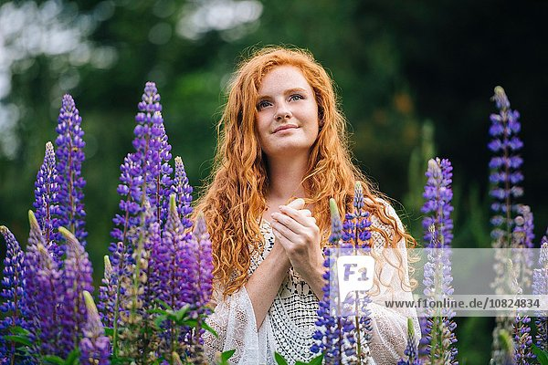 Serene young woman amongst purple wildflowers with hands clasped