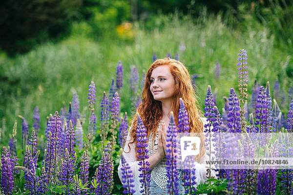 Serene young woman meditating with hands together amongst purple wildflowers